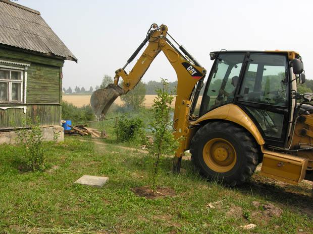 Ковшом снимают плодородный слой почвы